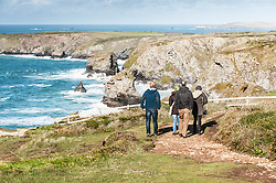 Walkers on the coastal path overlooking Bedruthan Steps in Cornwall.