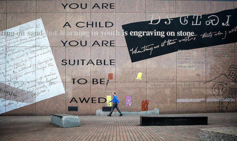 Jeffrey Rosenthal, senior workforce analyst with the North Carolina Department of Commerce, takes a walk around Government Mall on Aug. 4, passing the Education Wall, which was made for the Artwork for State Buildings Collection by American artist Vernon Pratt, titled 'Education Wall 1992', with words by Georgann Eubanks. The wall serves as an educational and inspirational piece of artwork made from sandblasted granite and stone colorants.