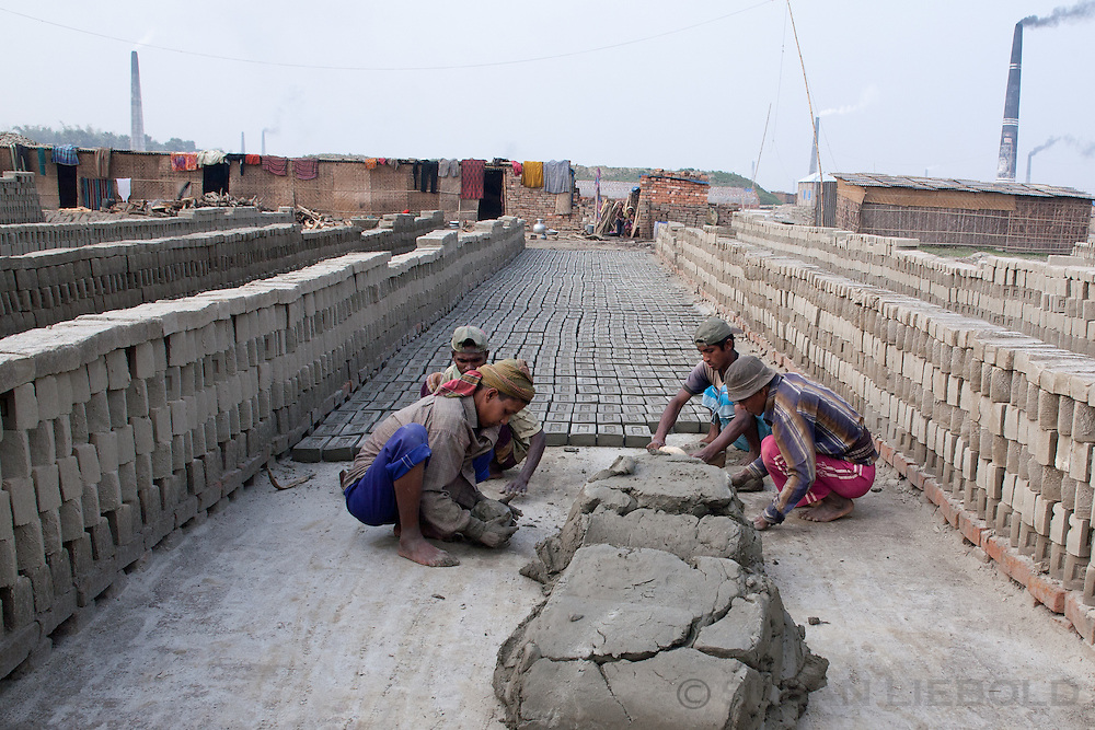 Men making the bricks in wooden molds. They leave them out to dry on the ground. Once dried they are carried to the kiln for burning. Bangladesh.