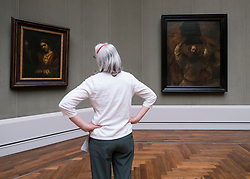 Woman looking at paintings inside Gemaldegalerie museum, at Kulturforum in Berlin, Germany