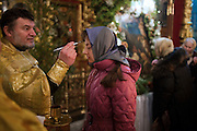 Moscow, Russia, 06/01/2011..A priest makes uses holy water to make the sign of the cross on a woman's forehead as Russian Christians attend an Orthodox Christmas service at Peter Paul church in central Moscow, late on Christmas Eve. Christmas falls on January 7 for Orthodox believers in the Holy Land, Russia and other Orthodox churches that use the old Julian calendar instead of the16th-century Gregorian calendar.