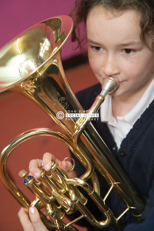 Primary school child learning to play the tuba in an after school club music lesson,