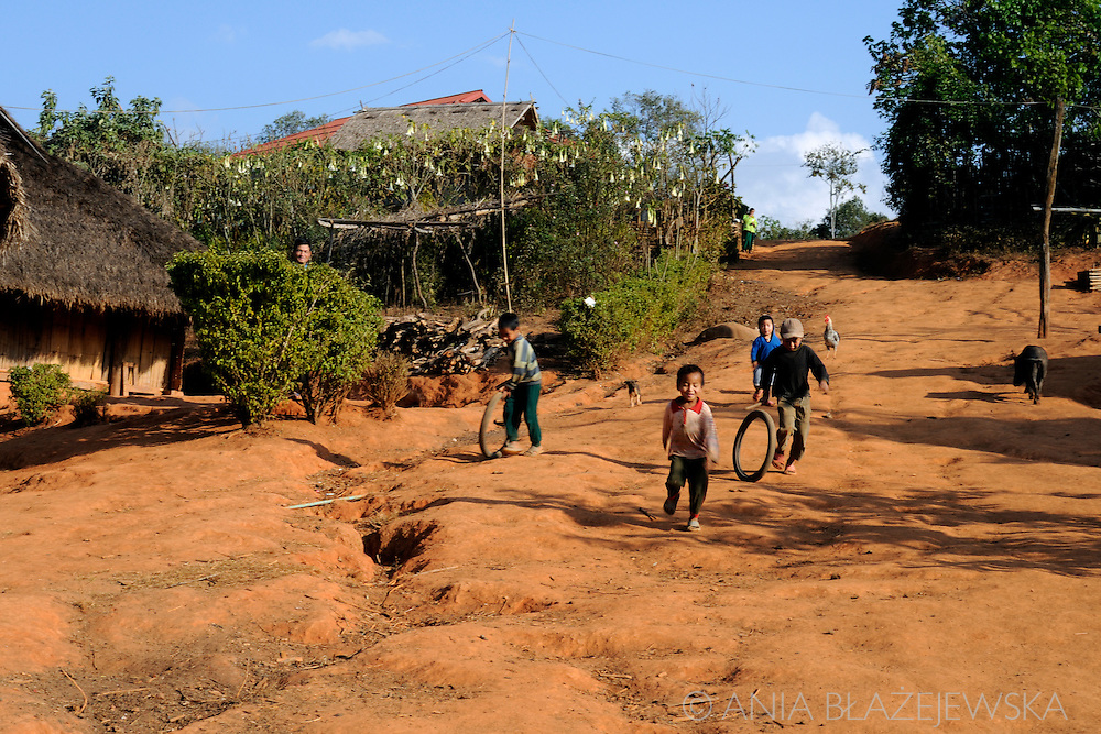 Burma/Myanmar, Golden Triangle. Boys playing with tyres in the Akha village.