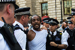 London, June 21st 2017. Protesters march through London from Sheherd's Bush Green in what the organisers call 'A Day Of Rage' in the wake of the Grenfell Tower fire disaster. The march is organised by the Movement for Justice By Any Means Necessary and coincides with the Queen's Speech at Parliament, the destination. PICTURED: A protester is arrested outside Parliament