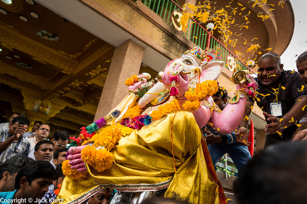 """15 SEPTEMBER 2013 - BANGKOK, THAILAND: Hindus in Bangkok load a deity of Ganesha onto truck to take it to the Chao Phraya River on the last day of Ganesha Chaturthi celebrations at Shiva Temple in Bangkok. Ganesha Chaturthi is the Hindu festival celebrated on the day of the re-birth of Lord Ganesha, the son of Shiva and Parvati. The festival, also known as Ganeshotsav (""""Festival of Ganesha"""") is observed in the Hindu calendar month of Bhaadrapada. The festival lasts for 10 days, ending on Anant Chaturdashi. Ganesha is a widely worshipped Hindu deity and is revered by many Thai Buddhists. Ganesha is widely revered as the remover of obstacles, the patron of arts and sciences and the deva of intellect and wisdom. The last day of the festival is marked by the immersion of the deity, which symbolizes the cycle of creation and dissolution in nature. In Bangkok, the deity (statue) was submerged in the Chao Phraya River.     PHOTO BY JACK KURTZ"""