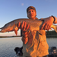 Ben Wiltsie displays a large northern pike he caught while fishing with his dog Evie.