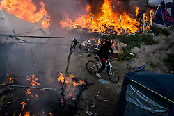 October 26, 2016 - Calais, France - A migrant rides a bike as fires burn inside the Calais 'Jungle' Wednesday. Fires burned at the camp overnight and during the day during the clearance work. France says that it has completed the operation to move thousands of migrants out of the ''Jungle.'' (Credit Image: © Markus Heine/NurPhoto via ZUMA Press)