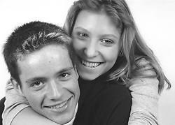 Studio portrait of teenage couple; girl with arms around boy; smiling,