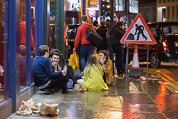 © Licensed to London News Pictures . 01/01/2015 . Manchester , UK . People sit on the pavement and eat McDonalds on Oxford Road . Revellers usher in the New Year on a night out in Manchester City Centre .  Photo credit : Joel Goodman/LNP