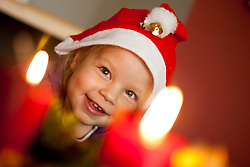 03.12.2011, Graz, AUT, Themenbild Advent, im Bild ein kleines Kind mit Weihnachtsmütze sitzt vor einem Adventkranz mit brennenden Kerzen und freut sich auf Weihnachten, EXPA Pictures © 2011, PhotoCredit: EXPA/ Erwin Scheriau