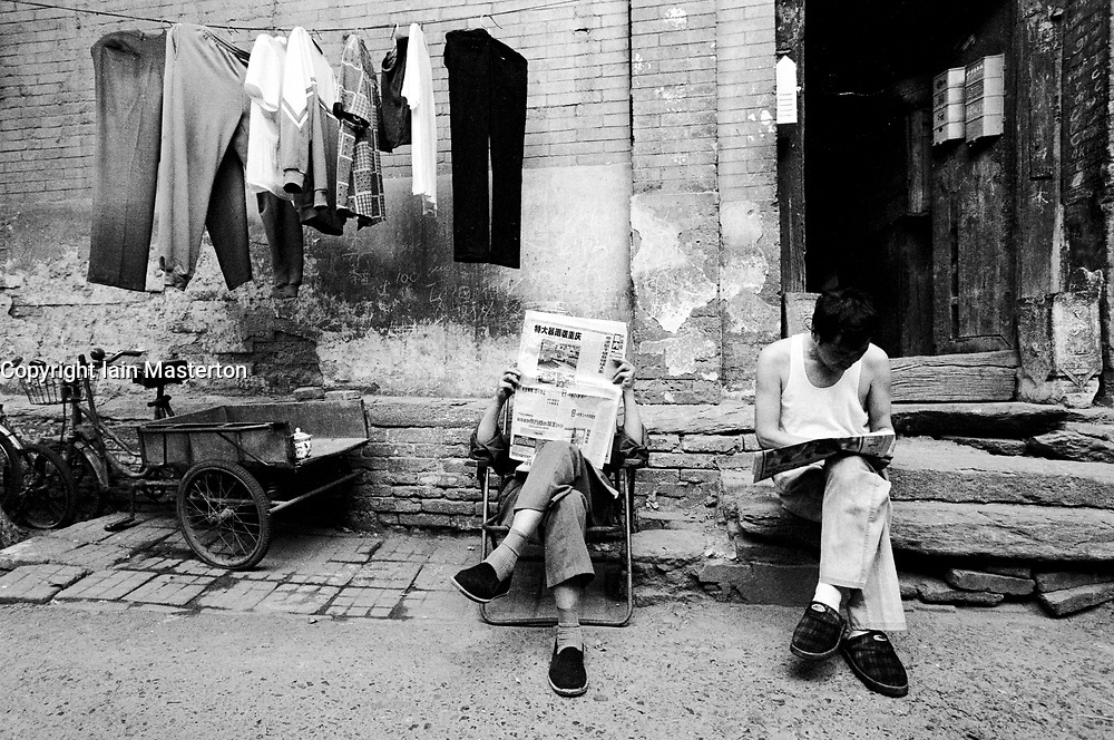 Men sitting outside old house in Beijing hutong