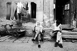 Men sitting outside old house in Beijing hutong