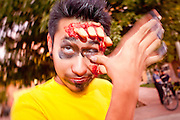"""Oct. 30, 2009 -- PHOENIX, AZ: Zombie MICHAEL GARCIA has a human hand coming out of his head and something stuck in his eye during the Zombie Walk in Phoenix. About 200 people participated in the first """"Zombie Walk"""" in Phoenix, AZ, Friday night. The Zombies walked through downtown Phoenix """"attacking"""" willing victims and mixing with folks going to the theatre and downtown sports venues.  Photo by Jack Kurtz"""