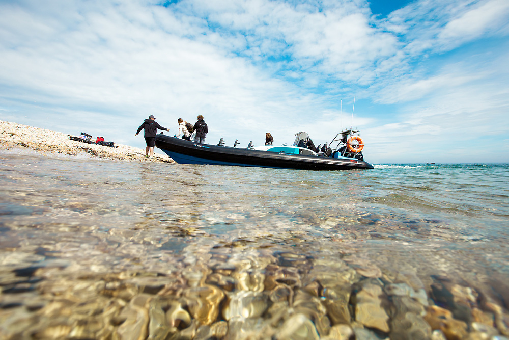 People arriving on a boat trip at the pebbly beach of the Ecrehous, a popular tourist attraction in Jersey, CI