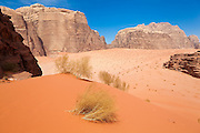 Red sand dunes and high sandstone cliffs in the desert of Wadi Rum, Jordan.