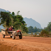 Man and woman driving a tractor and cart on rural road outside of Vang Vieng