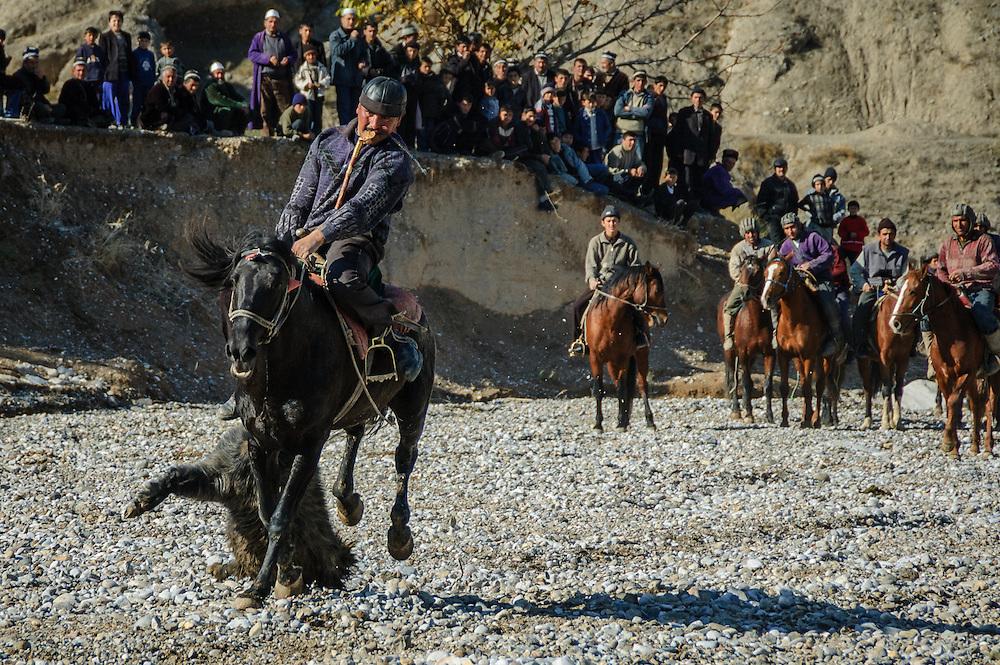 Image of a Tajik horseman charging off with the buz (a stuffed goat) toward the finish at a buzkashi event in the village of Kostarosh, northwest Tajikistan
