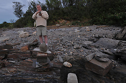 Potts Point South Harpswell Maine. Spontaneous Rock Sculpture Folk Art, Stack and Balance, as found on the Point in August 2009. Also known as Cairn Sculpture. Bill Greeley taking light measurements.