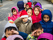 21 DECEMBER 2017 - HANOI, VIETNAM: Vietnamese schoolchildren, one wearing a Santa hat, in line to get into the Vietnam Military History Museum in Hanoi.   PHOTO BY JACK KURTZ