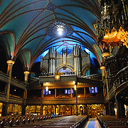 Looking back toward the entrance and pipe organ of the Notre-Dame Basilica in the heart of Old Montreal. With the exterior modeled loosely on the famous Notre Dame de Paris, when the second tower was completed in the 1840s, the Basilica was the largest church in North America. It features dramatic interior lighting and exceptionally ornate decorating throughout along with a pipe organ consisting of 9000 pipes.