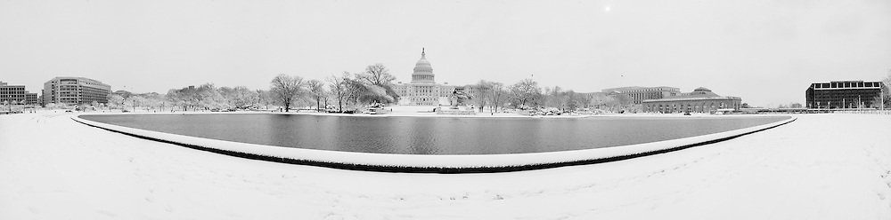 The Unites States Capitol  and reflectiong pool in snow, washington DC
