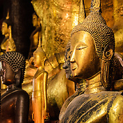 Gold leaf Buddha statues at Wat Mai Suwannaphumaham.  Wat Mai, as it is often known, is a Buddhist temple in Luang Prabang, Laos, located near the Royal Palace Museum. It was built in the 18th century and is one of the most richly decorated Wats in Luang Prabang.