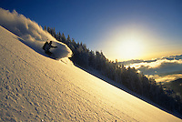 A snowboarder carves a turn in fresh powder on Teton Pass, Jackson Hole, Wyoming.