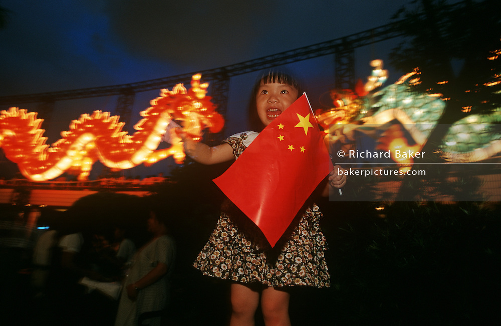 A young Hong Kong Chinese girl waves her newly-adopted national flag as Britain hands the territory back.