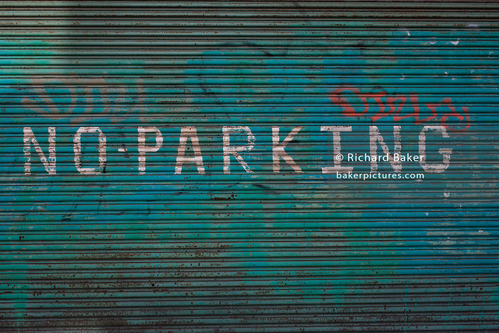A hand-painted No Parking notice on derelict shutters near 2012 Olympic Park site.