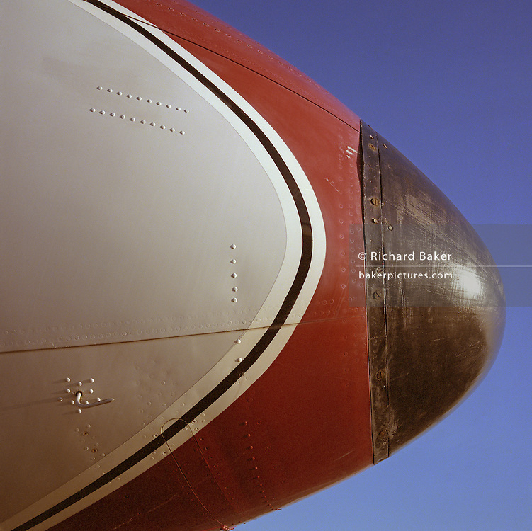 The nose detail of a de Havilland Comet in the colours of the long-defunct airline Dan Air is seen in profile at the Imperial War Museum's Duxford airfield, Cambridgeshire, England. The British de Havilland Comet first flew in July 1949 and is noted as the world's first commercial jet airliner as well as one of the first pressurized commercial aircraft. Early models suffered from catastrophic metal fatigue and the aircraft was redesigned. Here, the nose structure is held together with rivets that sit askew of the aircraft skin making it aerodynamically unfit to fly. It remains however, one of the classic and iconic designs in the history of commercial aviation. Picture from the 'Plane Pictures' project, a celebration of aviation aesthetics and flying culture, 100 years after the Wright brothers first 12 seconds/120 feet powered flight at Kitty Hawk,1903. .