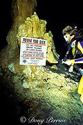 diver reads warning sign in The Carwash cenote, Akumal, <br /> Yucatan Peninsula, Mexico,   MR 117