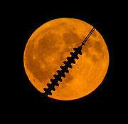 The moon shines through the cables of the electric tower.