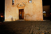 Night-time shadow of elderlyl woman of wall of Church of Saint Mark, Makarska, Croatia