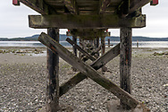 View from underneath the Fernwood Dock.  Photographed on the rocky beach near Fernwood Point on Salt Spring Island, British Columbia, Canada.