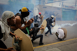 Group of opposition supporters are covered by the tear gas that are fired by the Bolivarian National Guard this May 3, 2017.