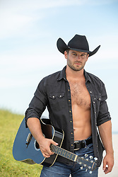 hot cowboy with open shirt holding a guitar outdoors
