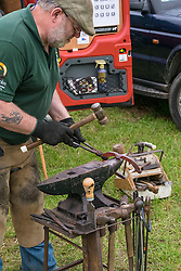 A farrier shaping a horseshoe at the Essex Country Show, Barleylands, Essex.