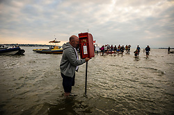 A man fixes a temporary post box during the annual Bramble Bank cricket match between The Royal Southern Yacht Club and the Island Sailing Club of Cowes, which takes place on a sandbank in the middle of the Solent.