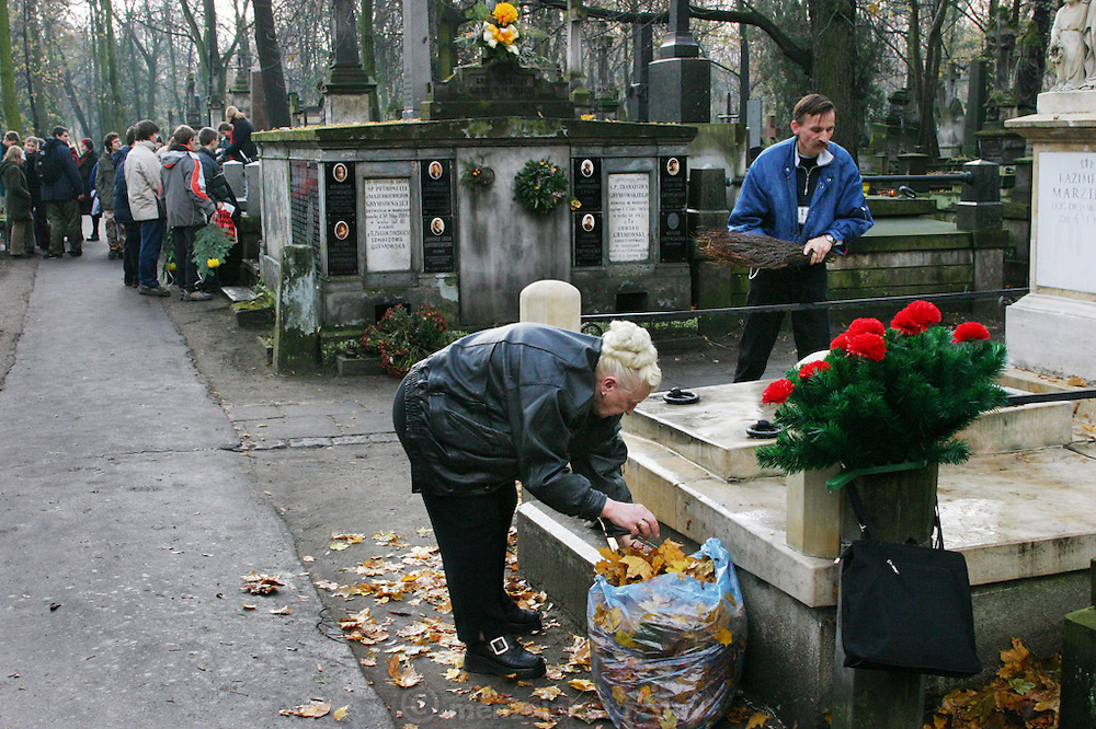 A woman cleans a grave preparing for All Saints Day. Powazek Cemetery. Warsaw, Poland.