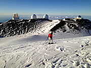 A man skis at the top of Mauna Kea on the Big Island of Hawaii. Mauna Kea is 13,796ft high but from from the bottom of the ocean, is the tallest mountain in the world at 33,500ft.  Due to its high altitude, dry environment and isolated geographical location, Mauna Kea's summit is one of the best sites in the world for astronomical observation. Since the creation of an access road in 1964, thirteen telescopes funded by eleven countries have been constructed at the summit.