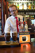 A barman with two pints of Guiness at Kehoe's pub, in Temple Bar, on 3rd April 2017 in Dublin, Republic of Ireland. Dublin is the largest city and capital of the Republic of Ireland.