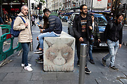 Tourists pass anti vehicle barriers made of concrete as part of the now familiar anti terror attack security in Leicester Square in London, England, United Kingdom.