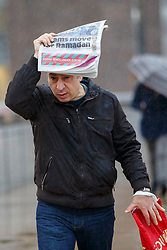 © Licensed to London News Pictures. 07/01/2016. London, UK. A commuter shelters himself with a newspaper during a heavy rain on London Bridge in London on Thursday, 7 January 2016. Photo credit: Tolga Akmen/LNP