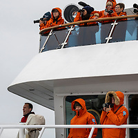 Guests in orange parkas watch wildlife from the National Geographic Orion ship while navigating the Southern Ocean between the Falklands and South Georgia Island.