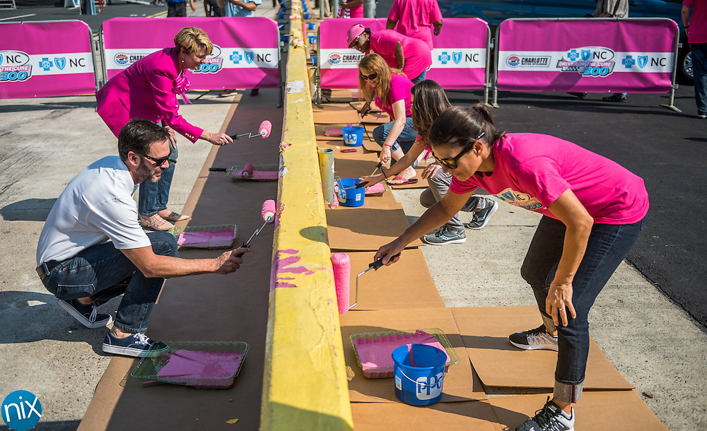 NASCAR driver Jimmie Johnson, left, joins former USA soccer player Mia Hamm, right, in painting Charlotte Motor Speedway's pit wall pink on Wednesday to promote breast cancer awareness.