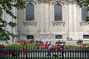 Wearing red school uniform jumpers, a group of schoolchildren enjoy warm sunshine during a day of outdoor learning beneath Wren architecture of St Paul's Cathedral in the City of London, the capital's financial district, on 23rd June 2021, in London, England.
