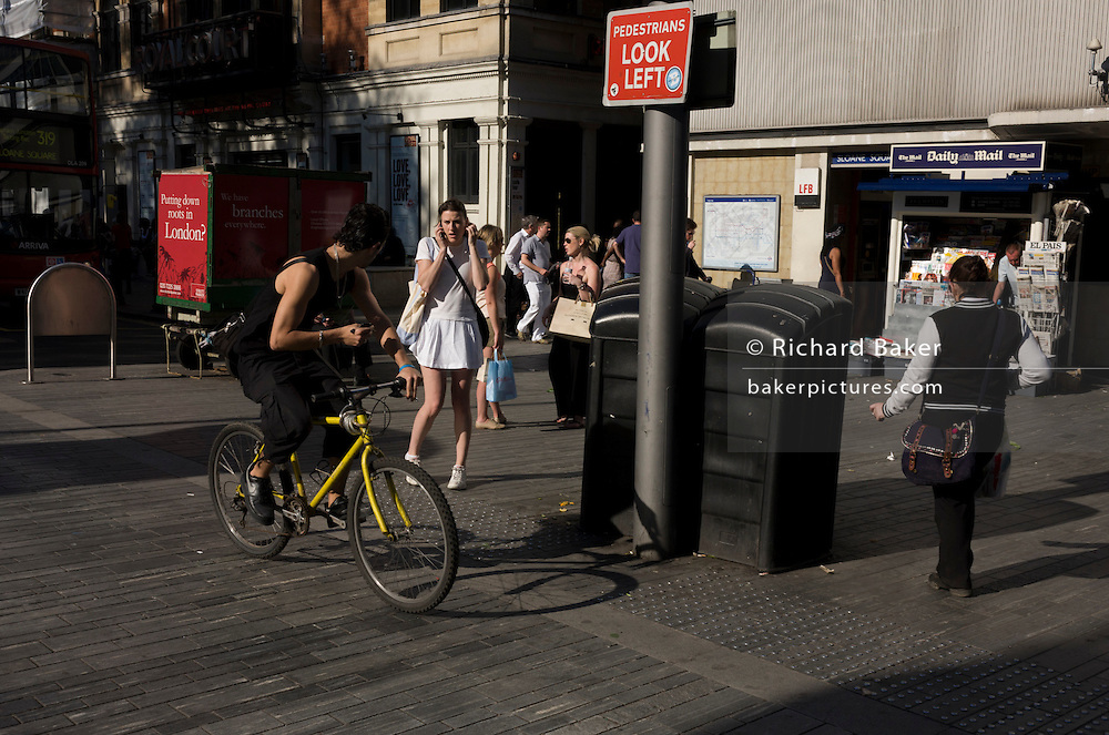 Passing cyclist looks backwards to short-skirted tennis player woman outside Sloane Square underground station.