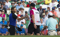 June 16, 2017 - Erin, WI, USA - Tommy Fleetwood, left, shakes handS with his caddie, Ian Finnis, after a birdie on the first hole during the second round of the U.S. Open on Friday, June 16, 2017, at Erin Hills in Erin, Wis. (Credit Image: © Mark Hoffman/TNS via ZUMA Wire)