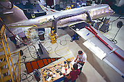"""Workers and aviation mechanics assemble a corporate jet aircraft. -MODEL RELEASED- Determine pricing and license this image, simply by clicking """"Add To Cart"""" below --"""