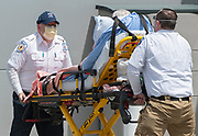 """FALMOUTH - Coastal Medical EMTs Lloyd Taylor, left, and Eric Fitchymeyer transport a patient from Falmouth Hospital to to their ambulance on Wednesday, April 22, 2019. """"It's all about the patient. Compassion is most important and it's the best medicine out there,"""" Erik Journet, operations clinical manager, said of the paramedic profession."""